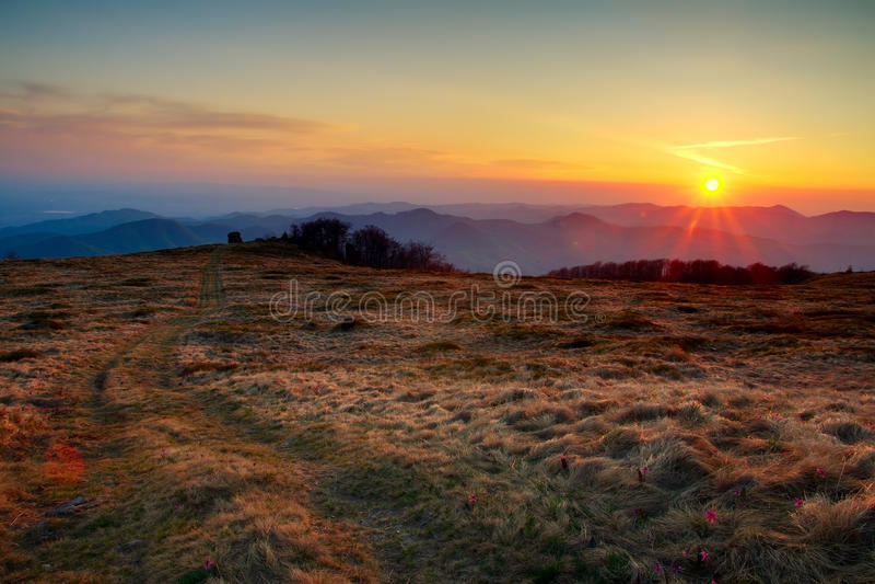 Mountain sunset. Beautiful mountain meadow sunset in high dynamic range stock image