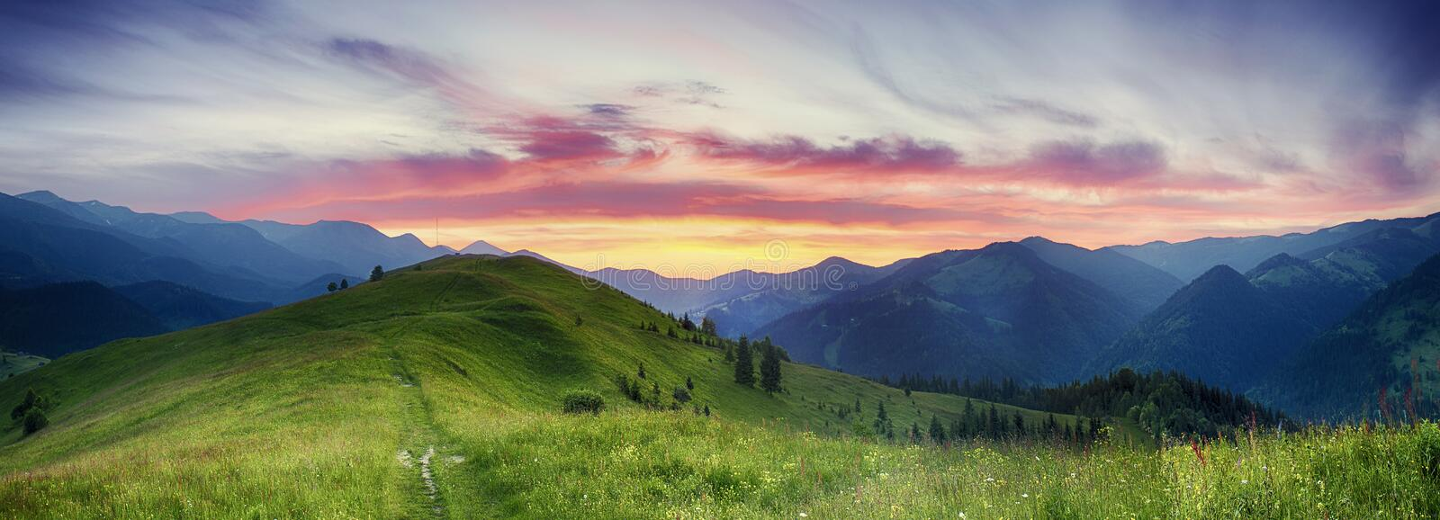 Mountain sunset. Carpathian mountains summer sunset landscape with dramatic sky and blue mountains stock photo