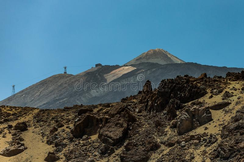 Mountain Teide with few white snow spots, under bright blue sky. Cableway on the left slope Teide National Park, Tenerife, Canary stock photography