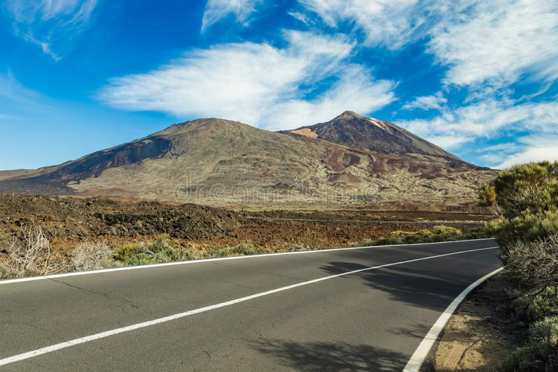 Mountain Teide, partly covered by the clouds. Bright blue sky. Teide National Park, Tenerife, Canary Islands, Spain stock image
