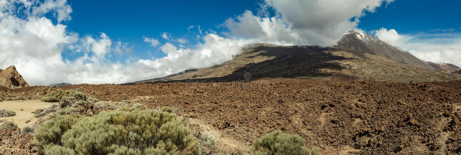 Mountain Teide with white snow spots, partly covered by the clouds. Bright blue sky. Teide National Park, Tenerife, Canary Islands stock photo