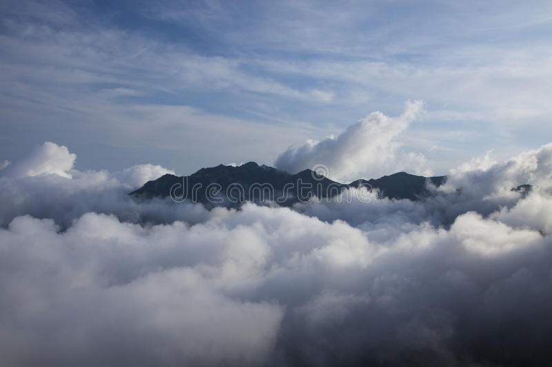 Mountain top over clouds royalty free stock images