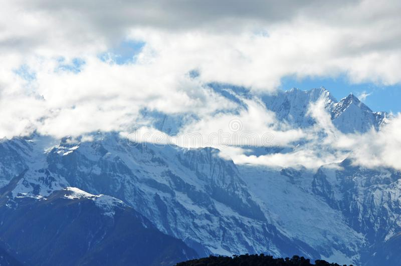 Meili Snow Mountain Mingyong Glaciers. The mountain top under the cloudy sky.Meili Xue Shan or Mainri Snow Mountain is a mountain range in the Chinese province stock photos