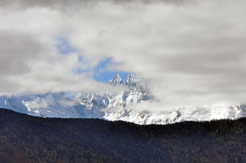 Meili Snow Mountain Mingyong Glaciers. The mountain top under the cloudy sky.Meili Xue Shan or Mainri Snow Mountain is a mountain range in the Chinese province royalty free stock photography