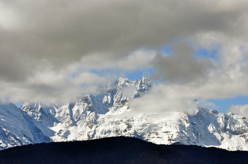 Meili Snow Mountain Mingyong Glaciers. The mountain top under the cloudy sky.Meili Xue Shan or Mainri Snow Mountain is a mountain range in the Chinese province stock image
