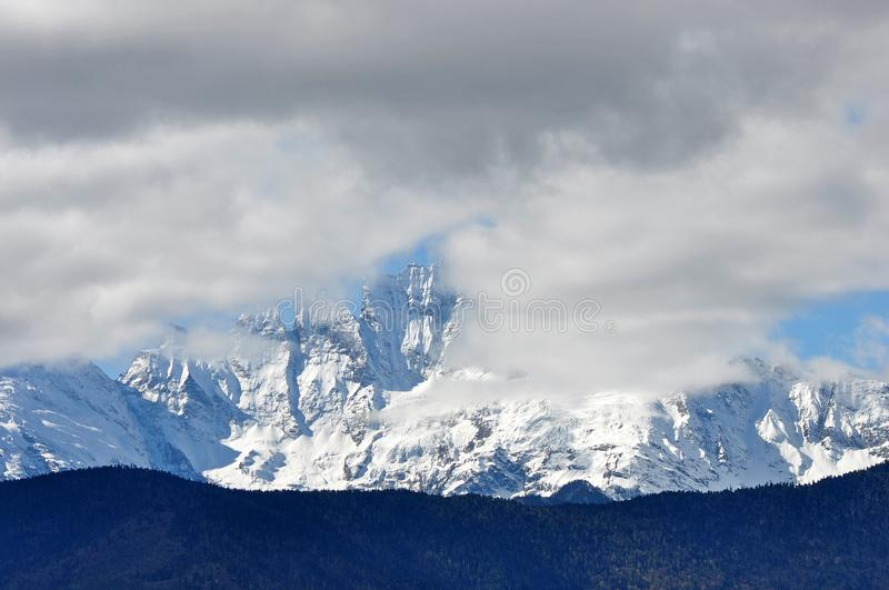 Meili Snow Mountain Mingyong Glaciers. The mountain top under the cloudy sky.Meili Xue Shan or Mainri Snow Mountain is a mountain range in the Chinese province royalty free stock photos