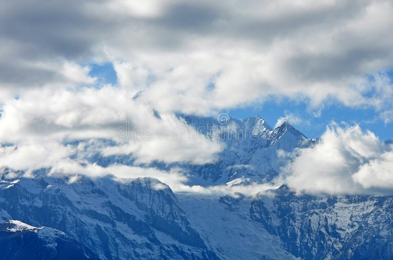 Meili Snow Mountain Mingyong Glaciers. The mountain top under the cloudy sky.Meili Xue Shan or Mainri Snow Mountain is a mountain range in the Chinese province royalty free stock images