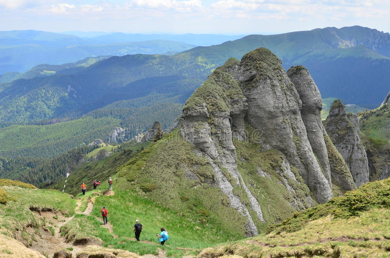 Mountain tourists. Ciucas Mountains, Carpathian Mountain Range, Romania - June 10, 2017: Tourists with backpacks passing by spectacular rock formations royalty free stock images
