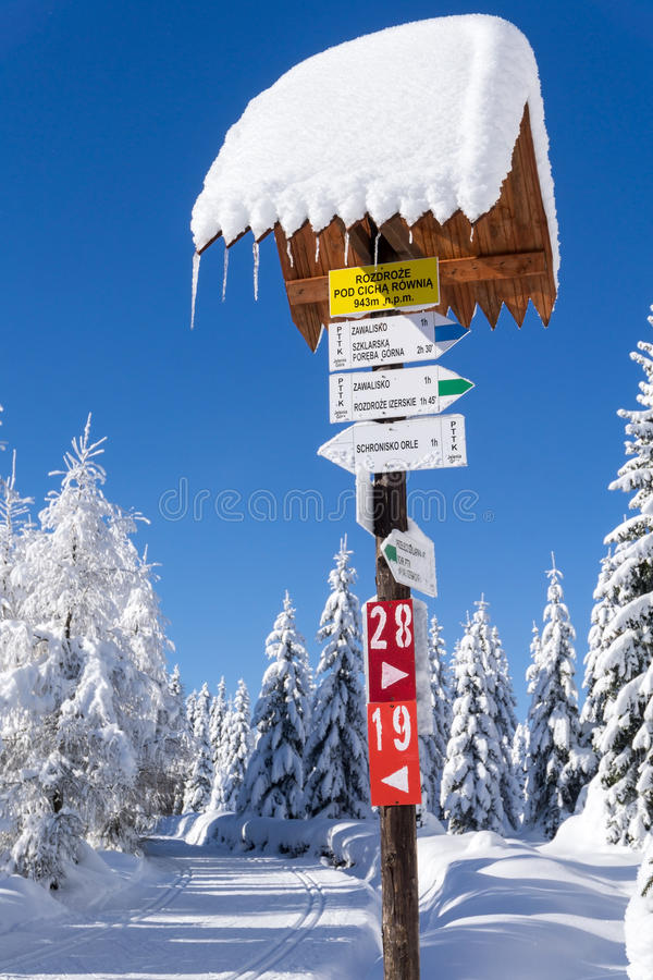 Mountain trail sign with directions and hiking or skiing time stock photos