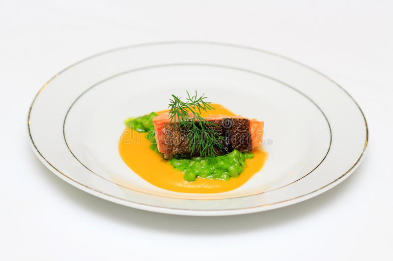 Mountain trout Orientale, stewed in orange sauce with green grain cream fitness. Side view royalty free stock photo