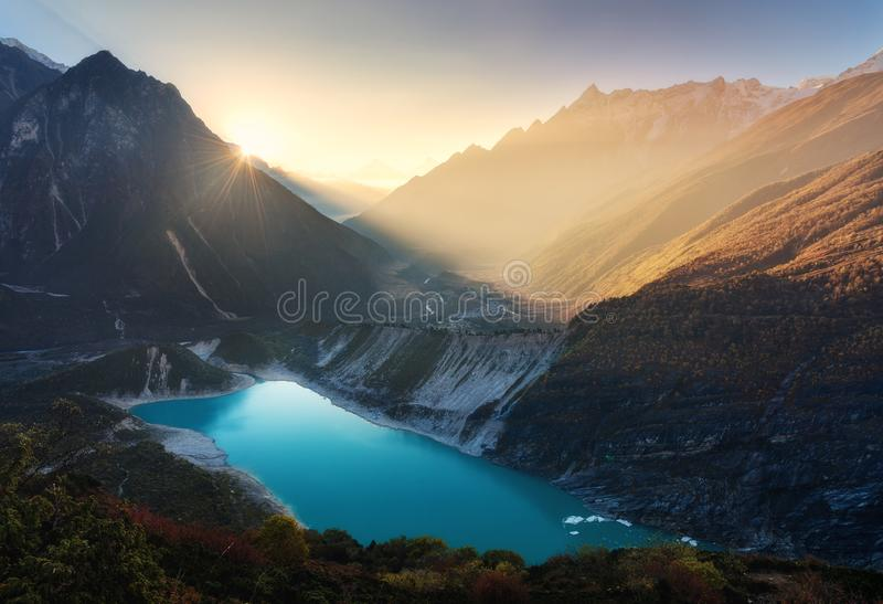 Mountain valley and lake with turquoise water at sunrise in Nepa. L. Majestical landscape with high mountains, lake, lightened hills, rocks, sun with yellow royalty free stock photos