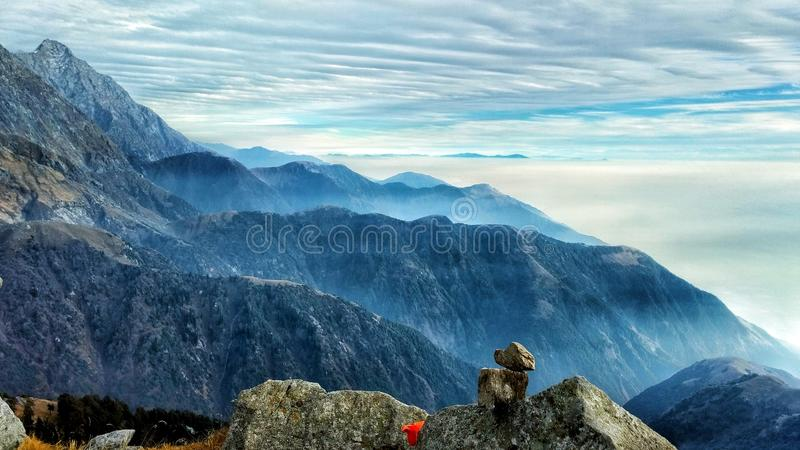 The Mountain and Valley. The Mighty mountain looks down to the Valley below which is entirely covered in morning mist and fog royalty free stock photos