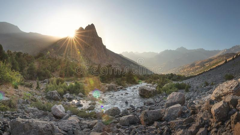 Mountain valley. Bright mountains nature landscape at sunrise. Mountain river and vivid sun rays behind mount peak. Scenic stock images