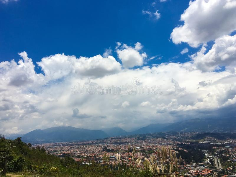 Mountain View and Bright Blue Sky with City of Cuenca Below. View of the hillside and mountains with bright blue sky and white fluffy clouds over the Andes royalty free stock photos