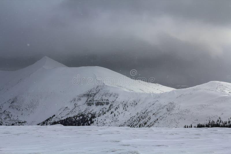 Mountain View d'hiver en montagnes carpathiennes avec les nuages dramatiques image libre de droits