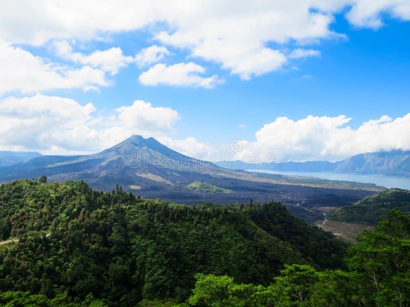Mountain View del volcán con el lago, bosque verde enorme, cielo azul y imagen de archivo libre de regalías