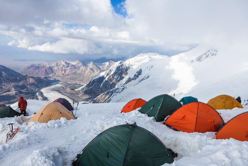 Mountain View do acampamento 4 do pico de Lenin Os montanhistas que preparam-se para a cimeira tentam em suas barracas fotografia de stock