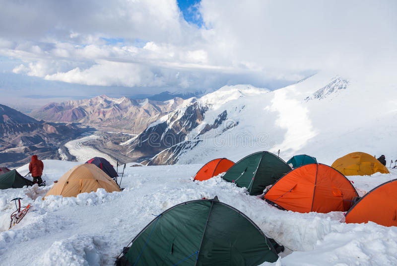 Mountain view from Lenin peak camp 4. Climbers preparing for summit attempt in their tents. Pamir mountains, Kyrgyzstan stock photography