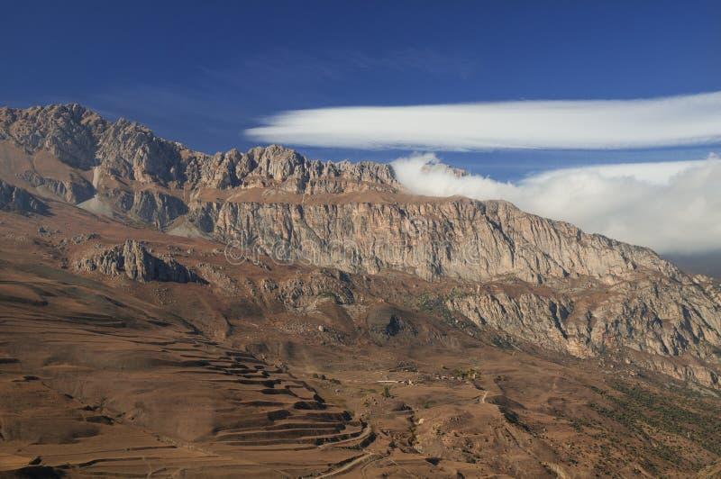 Mountain View maestoso - picchi rocciosi con i pendii erbosi appassiti brunastri sotto cielo blu con le nuvole ciecamente bianche immagine stock