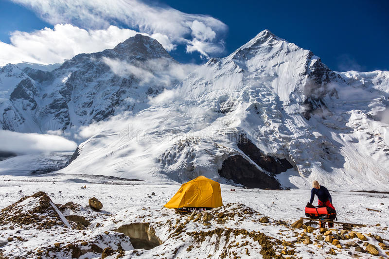 Mountain View Orange Tent Alpinist Holding Backpack stock photo