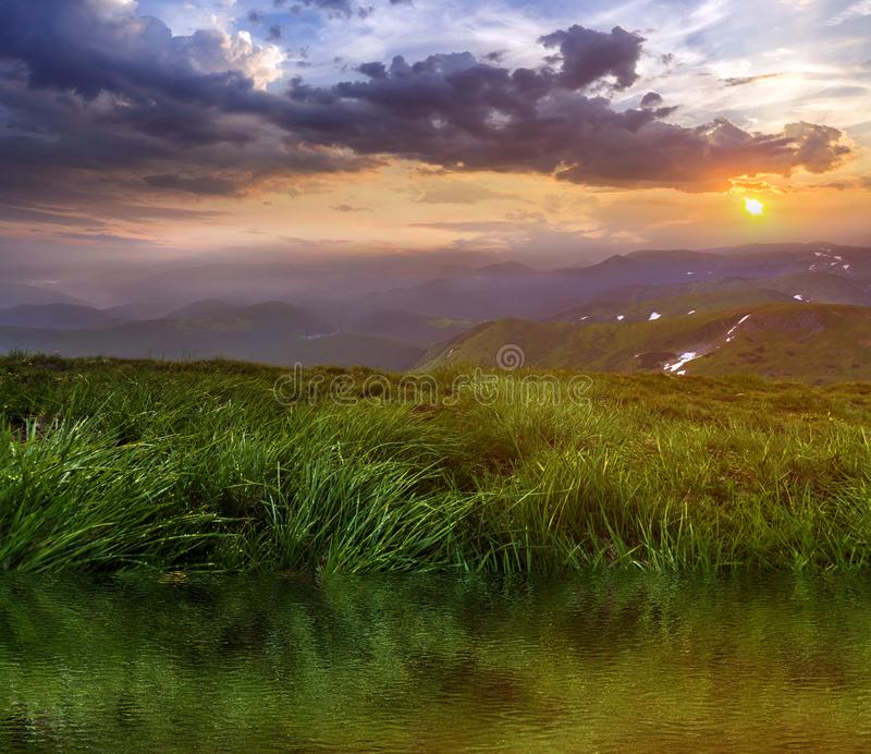 Mountain view at sunset or sunrise. Panorama of green grassy valley reflected in clear lake water, foggy mountains range with snow. Patches, dramatic cloudy sky stock photo