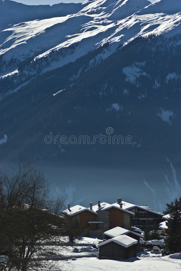 Mountain village verbier. View of verbier in the swiss alps on perfect crisp winters day, perspective compression from extreme telephoto lens stock photography