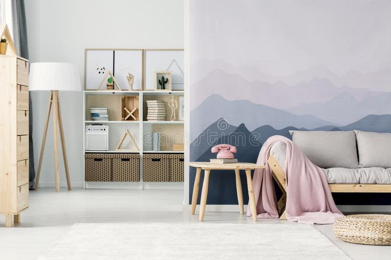 Mountain wallpaper in living room. Pink phone on wooden table next to a beige sofa in living room interior with mountain wallpaper stock photo