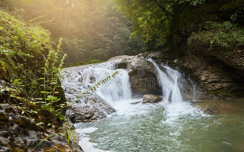 Mountain waterfall in the forest, a large noisy stream of water. A wild natural spring in a remote place stock photos