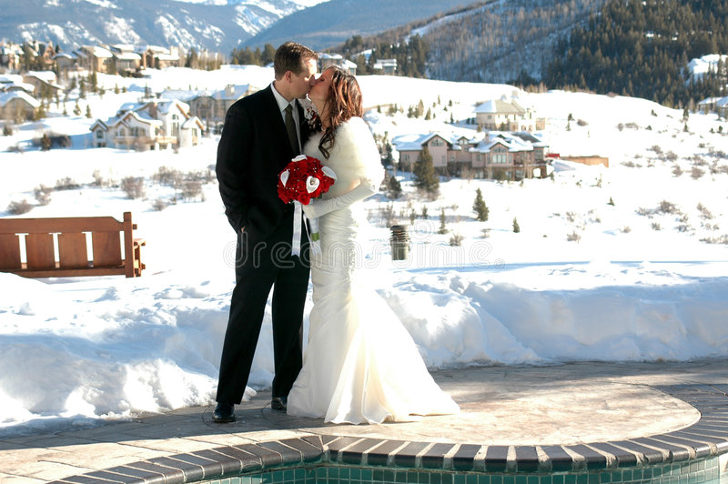 Mountain Wedding. Bride and Groom in the winter snow after their wedding. Bridal portrait royalty free stock photo