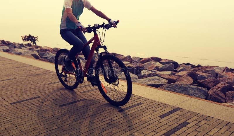 Mountainbike för kvinnacyklistridning på sjösidavägen royaltyfri bild