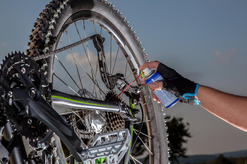 Mountainbike maintenance. A man is using a Oil spray to lubricate the chain from his mountainbike royalty free stock image
