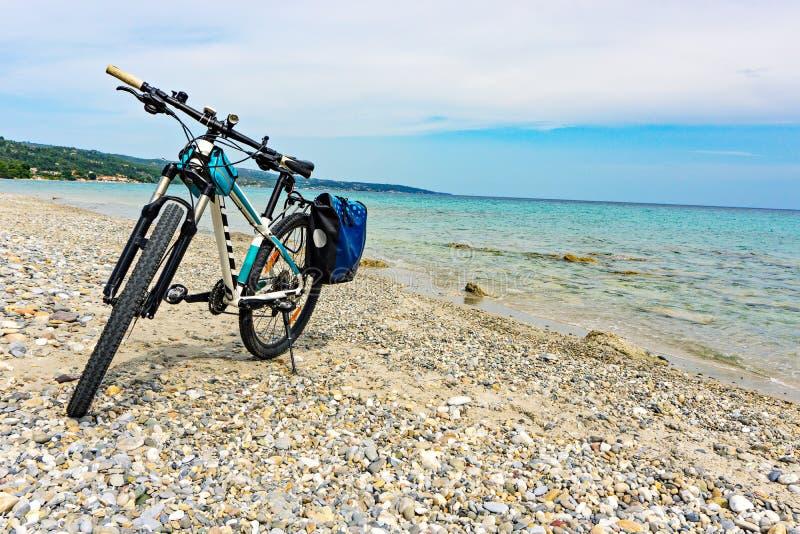 Mountainbike med påsen vid havet som parkeras på stranden royaltyfria bilder