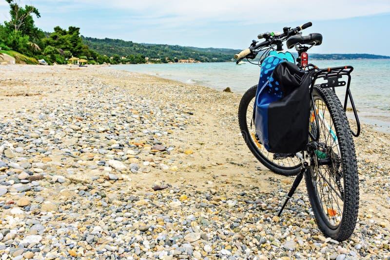 Mountainbike med påsen vid havet som parkeras på stranden arkivfoto