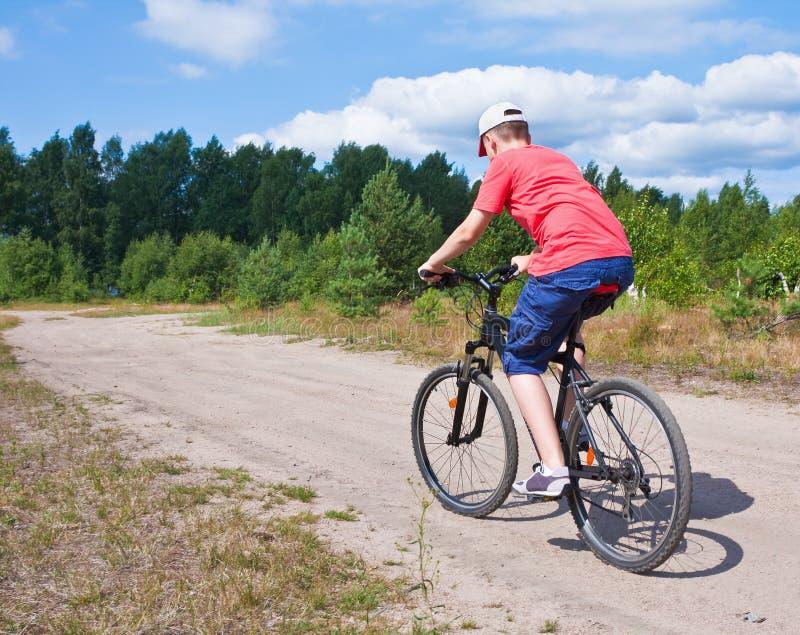 Mountainbikejugendlicher mit blauem Himmel stockbild