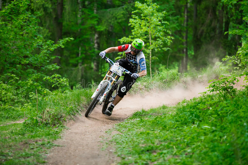 Mountainbiker reitet durch grünen Wald AM REAKTOR-SCHALEN-Wettbewerb lizenzfreie stockfotografie