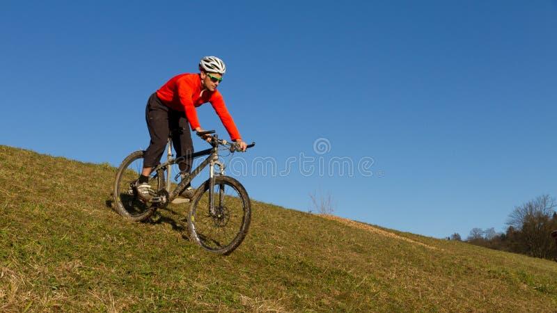 Mountainbiker sur un pré photo stock