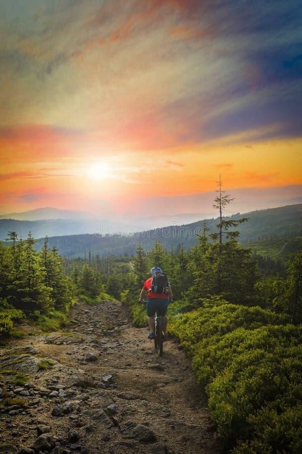 Mountainbikerreiten bei Sonnenuntergang auf Fahrrad in den Sommerbergen Vorder stockfoto