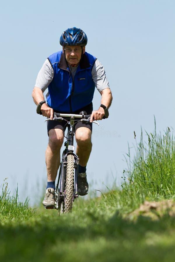 Mountainbiking aîné photographie stock
