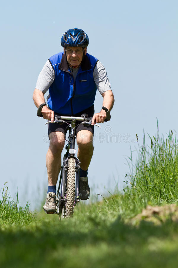 Mountainbiking sênior fotografia de stock