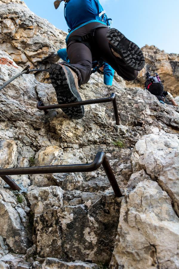 Mountaineer ascending on metal steps. Climbing Brenta Doloimtes, Sentiero delle Bocchette Alte stock images