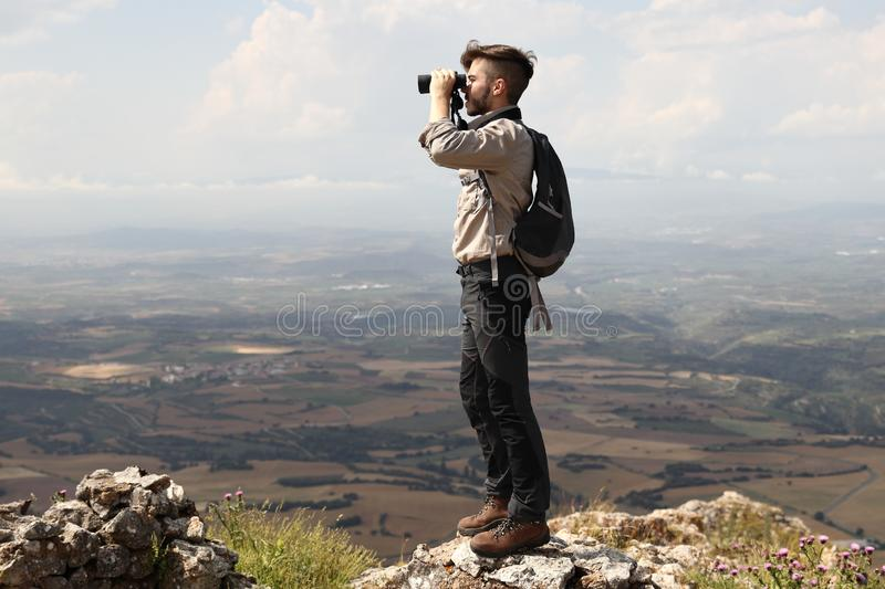CLIMBER BOY WITH BACKPACK LOOKING WITH BINOCULARS  FROM THE SUMMIT OF THE MOUNTAIN ON SUMMER HOLIDAY stock image