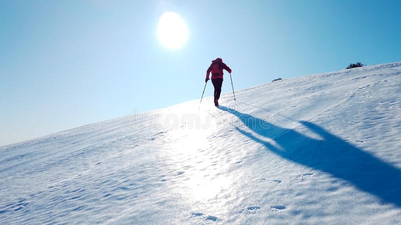 Mountaineer climbs a snowy mountain over blue clear sky. Winter stock photography