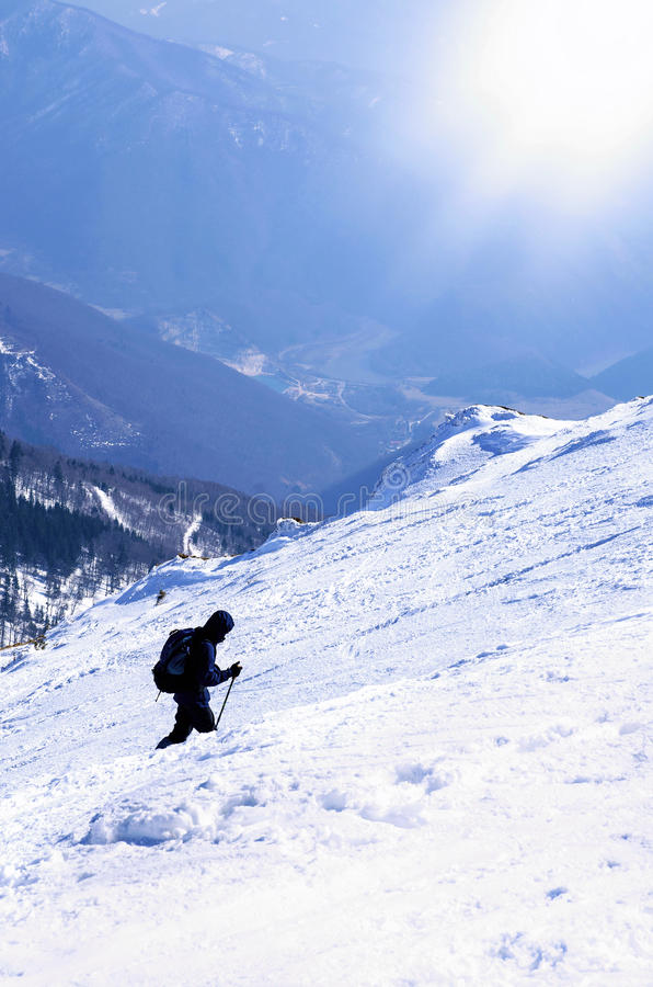 Mountaineer goes on trip to the top of a snowy mountain in a sunny winter day royalty free stock photography