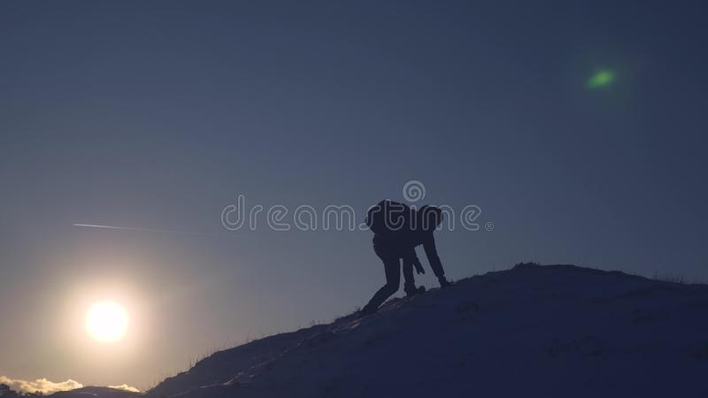 Mountaineer Journey to mountains in winter. Traveler climbs mountain peak. tourist stands on a high snowy mountain stock photo