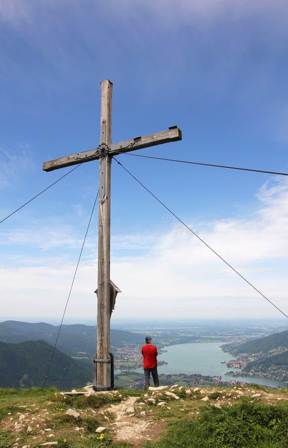 Mountaineer and mountain cross, beautiful view over lake tegernsee, bavaria, germany. Mountaineer standing beside mountain cross, beautiful view over lake stock photos