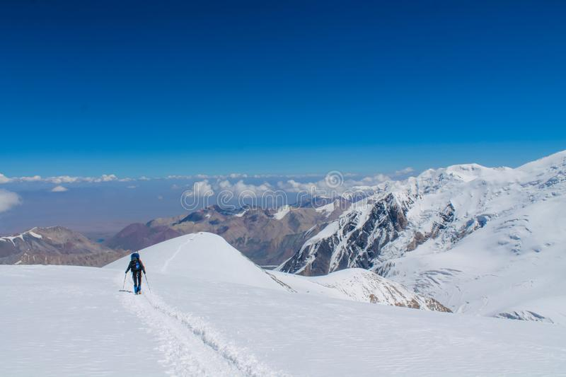 Mountaineer on the snow of mountain glacier in Himalaya summit ascent. Mountaineers on snow of mountain glacier, climbing alpinist route. Alpinist with equipment stock images