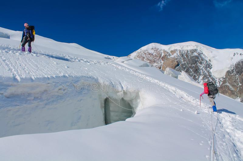 Mountaineer on the snow of mountain glacier in Himalaya summit ascent. Mountaineers on snow of mountain glacier, climbing alpinist route. Alpinist with equipment stock photography