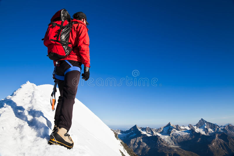 Mountaineer on a snowy ridge. Mountaineer on the snowy ridge of Breithorn, looking at the peaks around Zermatt with the Weisshorn. Switzerland, Europe royalty free stock photos