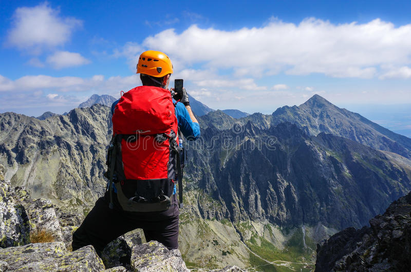 Mountaineer taking picture with smartphone in the mountains royalty free stock photo