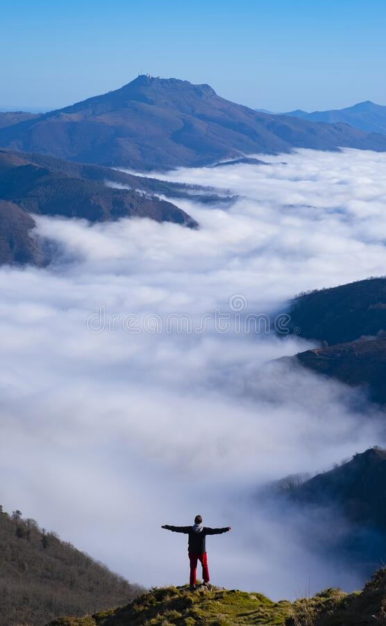 Mountaineer on top of the mountain with sea of clouds in the background, Aiako Harriak Natural Park, Euskadi stock photos